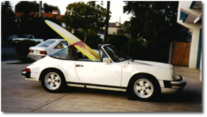 White Porsche 911 Targa with a longboard in passenger seat parked in San Clemente